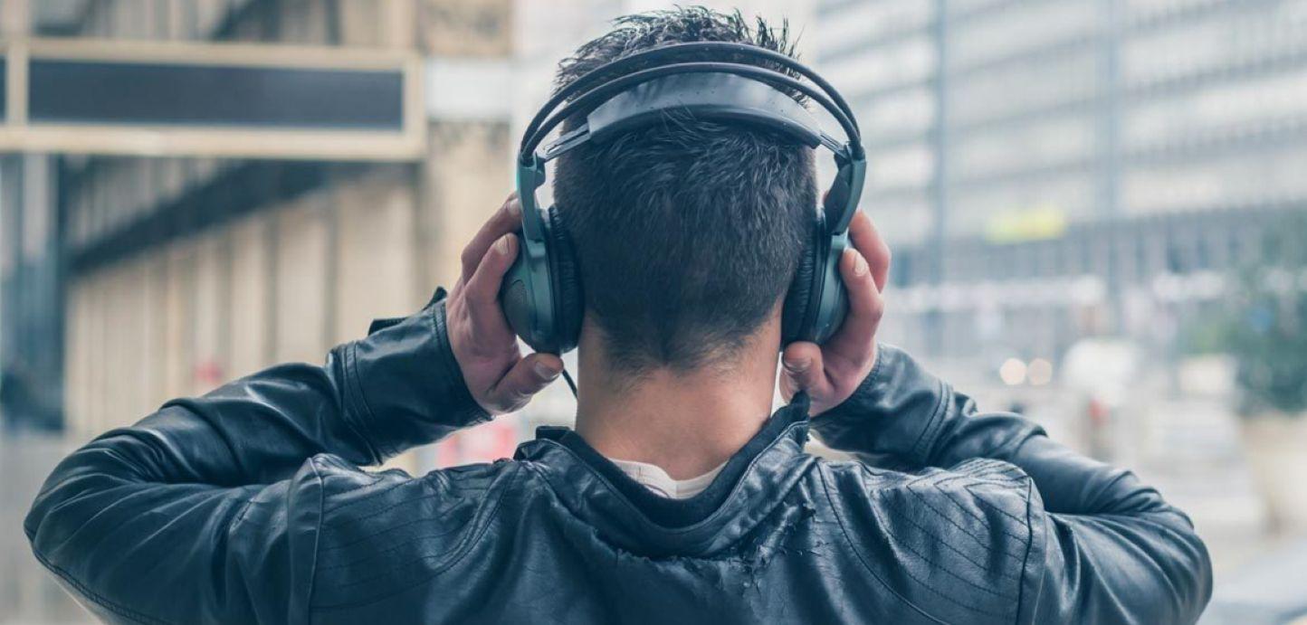 male worker wears headphones - 1444×691